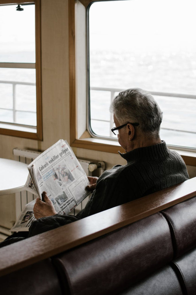 an older adult reading a newspaper while on a cruise boat