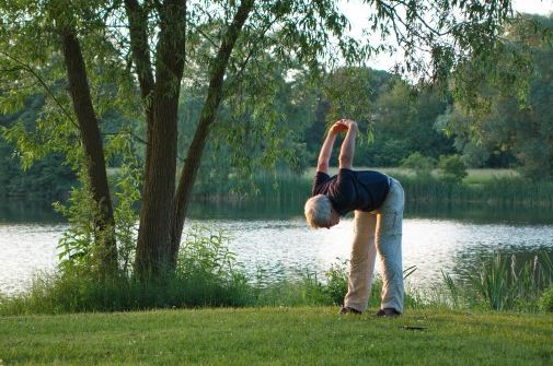 An elderly person doing yoga outdoors